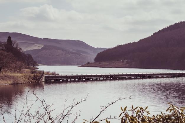 Vista mozzafiato di una galleria sulla superficie di un lago circondato da colline alberate