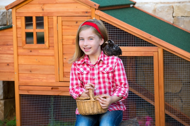 Breeder hens kid girl rancher farmer with chicks in chicken coop