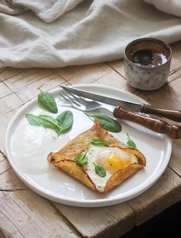 Бретонские гречневые блины с яйцом, шпинатом и сливками, поданные с кофе. деревенский стиль