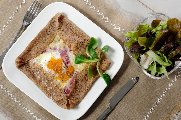 Breton crepe with egg in white plate