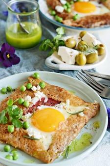 ハム、チーズ、卵、フェタチーズ、グリーンピース、グリーンバターを使ったそば粉から作られたブルトンの伝統的なパンケーキ。
