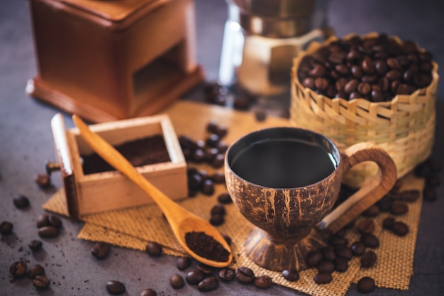 Brew black coffee in coconut cup and morning lighting. roasted coffee beans in a bamboo basket and wooden spoon.