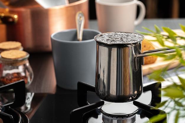 Заваривать кофе в стальной турке на газовой плите крупным планом
