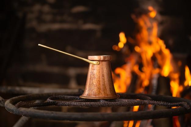 Заварить кофе в турке на открытом огне. концепция уютной атмосферы и напитков.