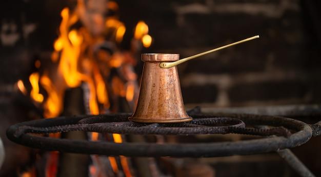 Prepara il caffè in un turco su un fuoco aperto. il concetto di un'atmosfera accogliente e bevande.
