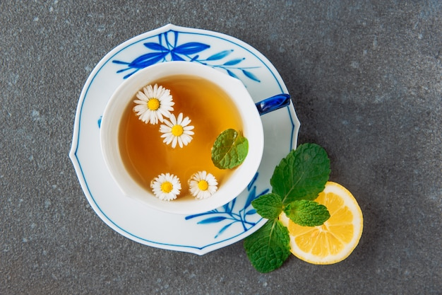 Brewed chamomile tea with half of lemon and green leaves in a cup and saucer on grey stucco background, top view.