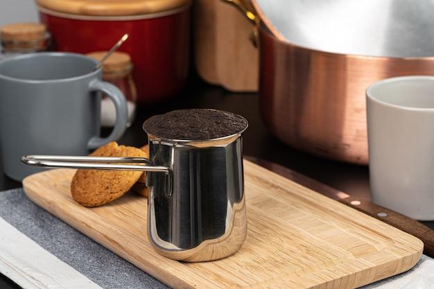 キッチンカウンターの金属タークで淹れたてのコーヒーをクローズアップ