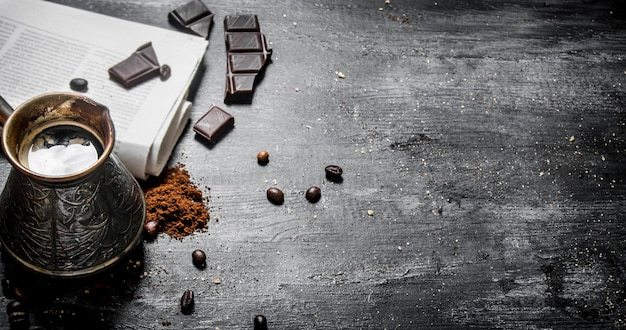 木製のテーブルに新鮮な新聞とビターチョコレートを入れた淹れたてのコーヒーポット。