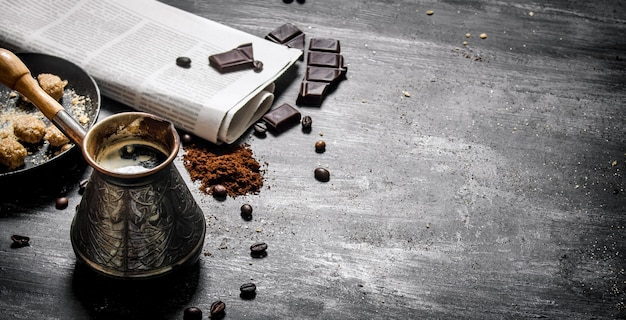 Brewed coffee pot with fresh newspaper and bitter chocolate.