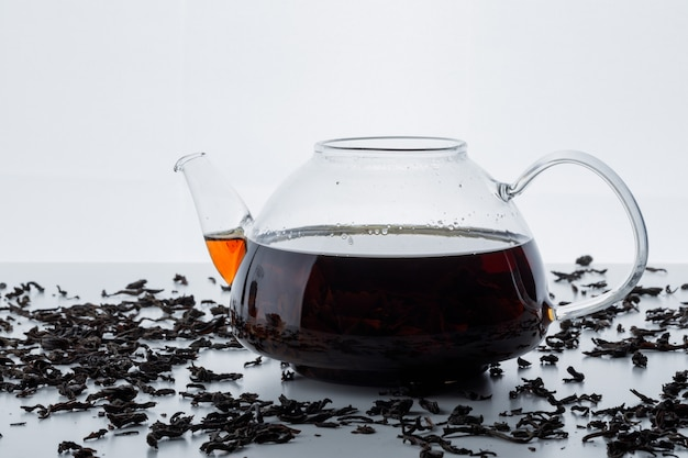 Brewed tea in a glass teapot with dry black tea side view on a white surface