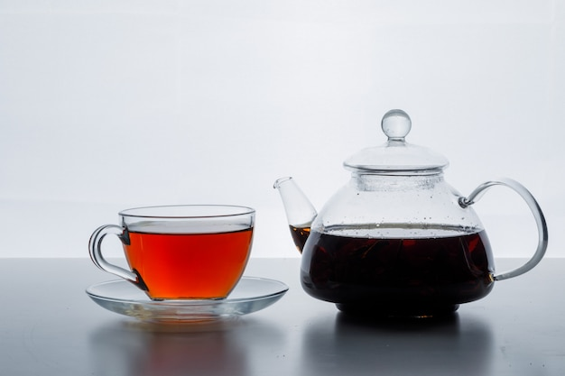 Brewed tea in teapot and cup side view on a white gradient surface
