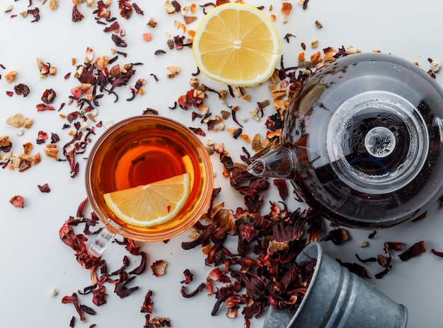 Brewed tea with dried herbs, lemon in glass and teapot on white surface