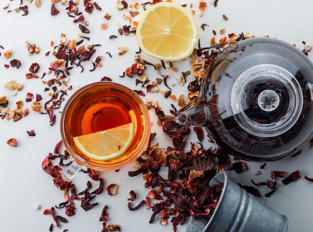 Tè preparato con erbe secche, limone in vetro e teiera sulla superficie bianca