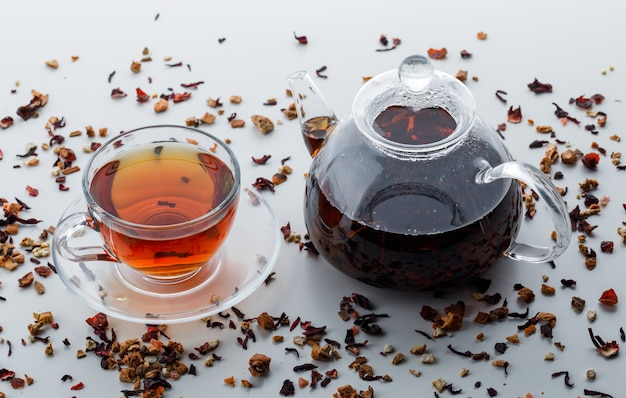 Brewed tea with mixed dried herbs in teapot and cup on white surface