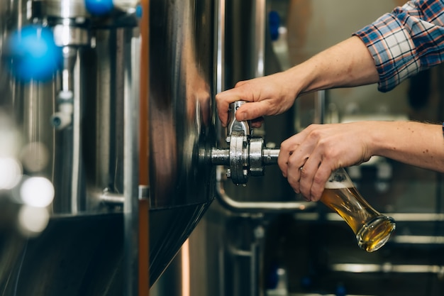 Brewer filling beer in glass from tank at brewery. family business concept.