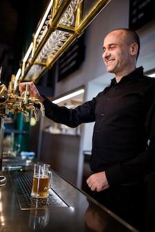 Пивовар разливает пиво в пивной бокал из пивного насоса
