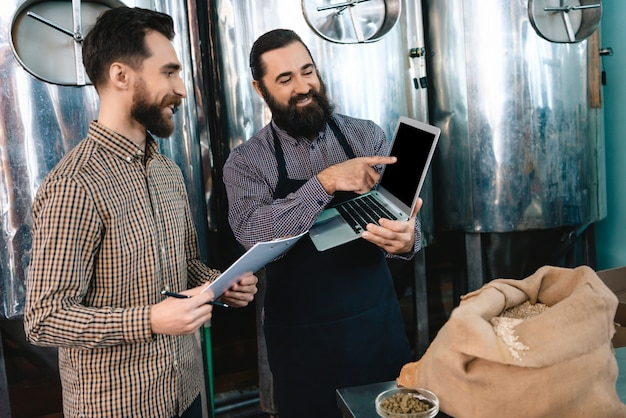 Brewer man points to laptop screen microbrewery
