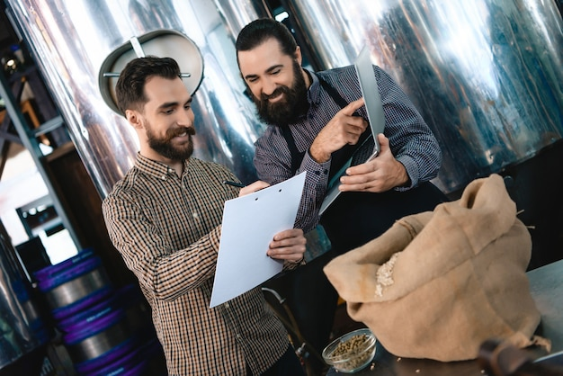 Brewers with laptop and clipboard at microbrewery.