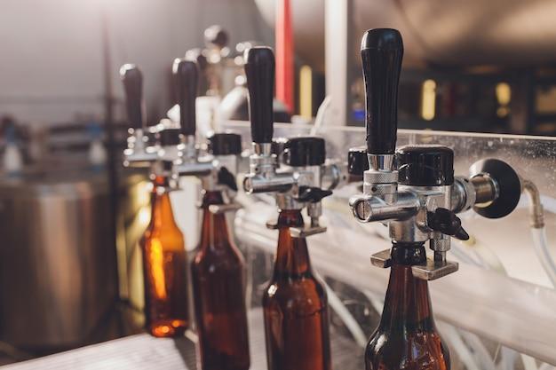 Пивоваренный завод разливает пиво в стеклянные бутылки на конвейерные линии. промышленные работы, автоматизированное производство продуктов питания и напитков. технологические работы на заводе.