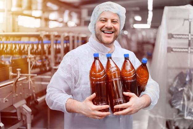 Работник пивоварни с бутылками пива в руках на упаковочной линии