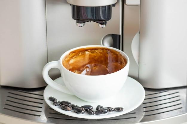 エスプレッソマシンから淹れたてのコーヒーを淹れます。予算のコーヒーメーカー。コーヒー豆で飾られた白いカップ。