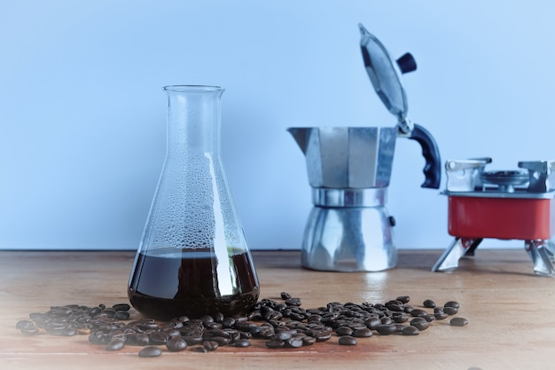 Brewing hot coffee in lab tube with coffee bean on wood table.