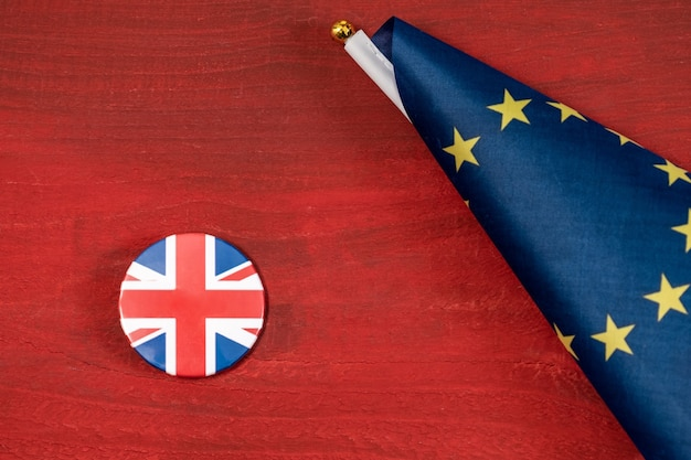 Brexit, european union flag with great britain flag on a jacket icon together on a red wooden table.