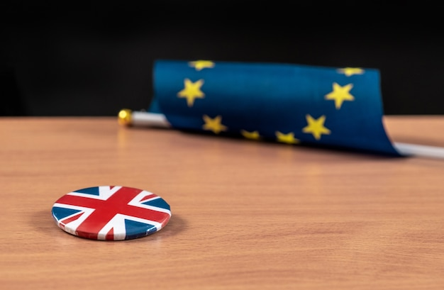 Brexit, european union flag with great britain flag on a jacket icon together on a table.