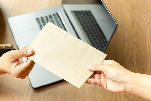 パートナー破損概念から茶色の封筒で賄briのお金を取るビジネスマン。