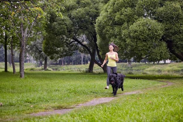 Briard와 여성 주인은 낮에 걷는 동안 공공 공원에서 달리고 있습니다.