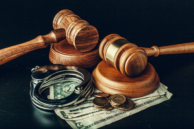 Bribe concept. dollar banknotes, handcuffs and gavel on dark black table
