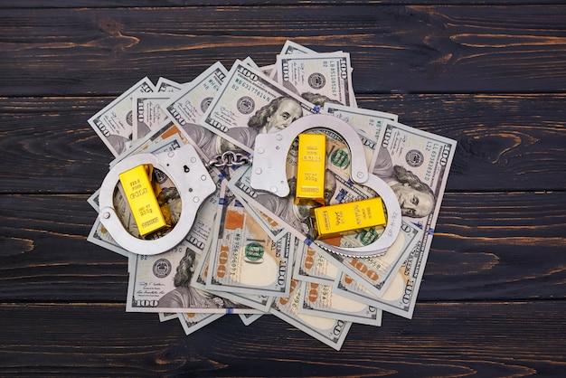 賄賂の概念、金の棒とドル紙幣の手錠