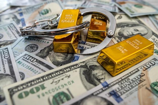 賄賂の概念の金の延べ棒とドル紙幣の手錠