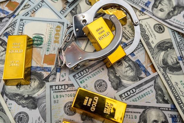 賄賂の概念の金の棒とドル紙幣の手錠