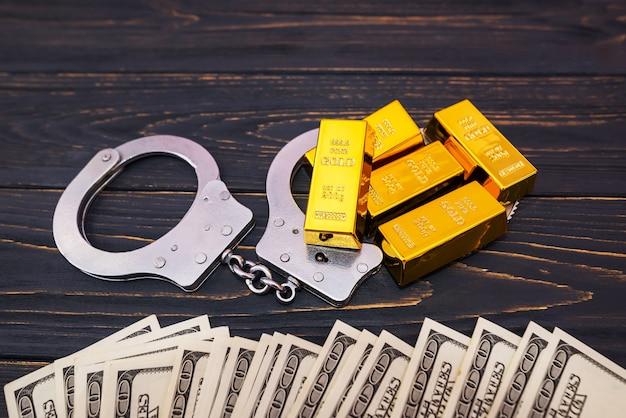 Bribe concept, gold bars and handcuff in dollar bills