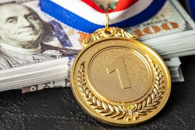 승리를 위해 스포츠에서 뇌물. 금메달 수상과 돈 달러의 스택입니다.