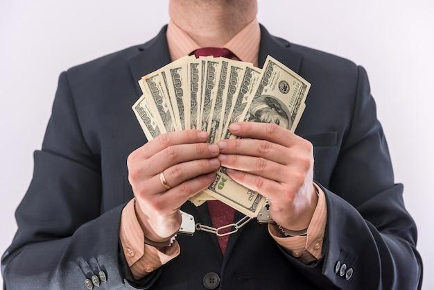 뇌물 또는 부패 개념 남성 손에 수갑에 달러 지폐를 잡아. 범죄자