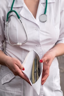 賄賂、お金でいっぱいの封筒を持つ医師の手