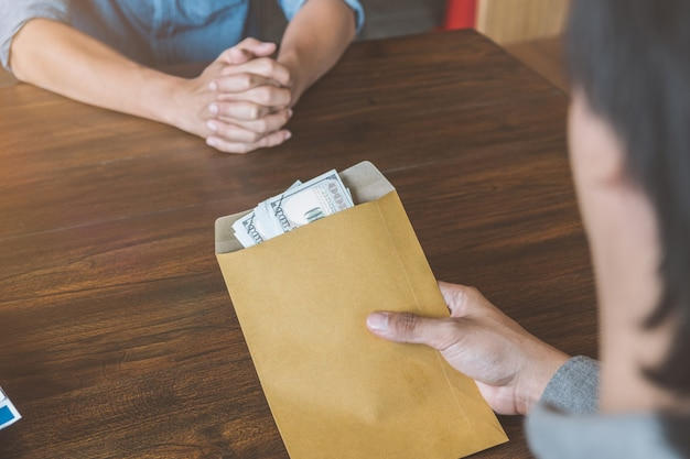 Bribery, a man giving bribe money in a brown envelope to another businessman