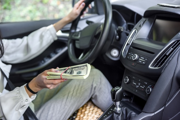 Bribery. woman sitting in driver seat and giving dollar bundle