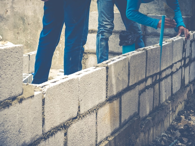 Кирпичные строители строят стены