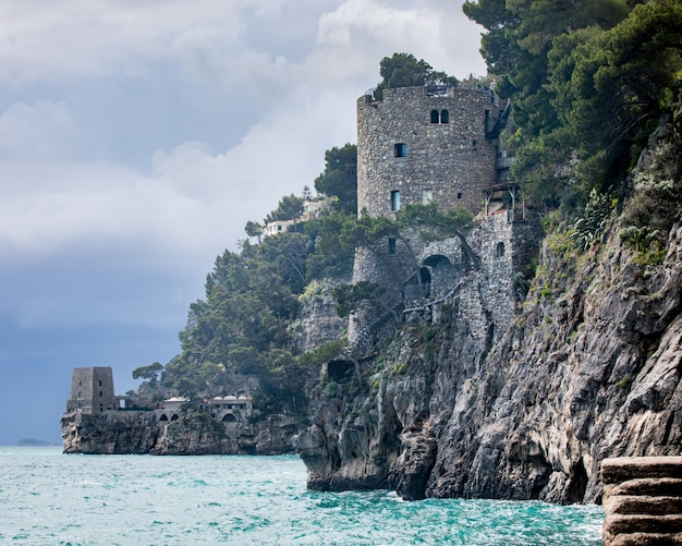 Brick castle on the edge of a cliff over the ocean captured in amalfi coast
