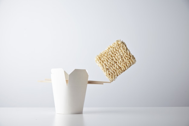 Brick of dry noodles balances on the edge of chopsticks on blank takeaway box isolated on white commercial retail set