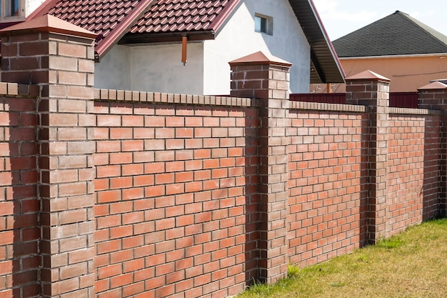 벽돌 울타리. 보호 벽돌 벽. 집 밖의