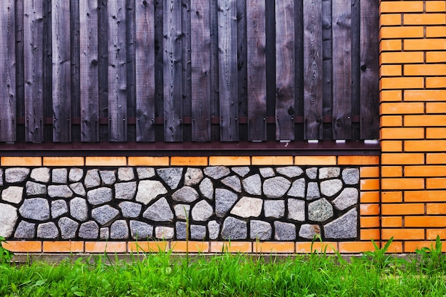 Brick fence with wooden spans and gray gravel
