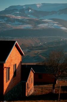 雪に覆われた山を越えたレンガ造りの家