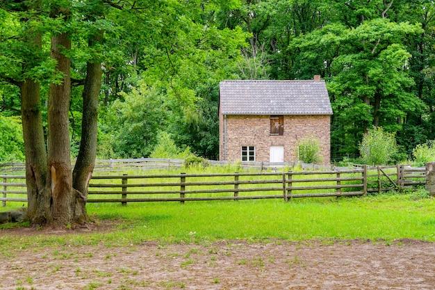ドイツ、アイフェル地域のコマーン村にある野外博物館の緑の木々に囲まれたレンガ造りの家