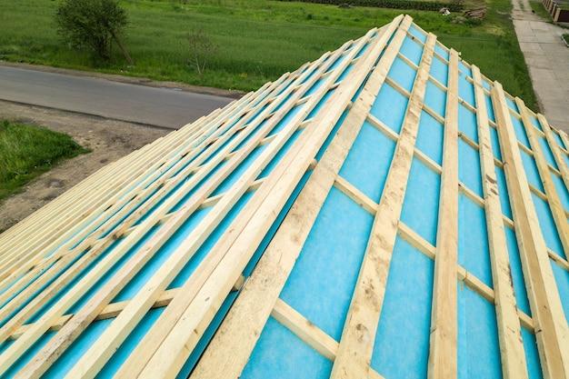建設中の木製の屋根フレームとレンガ造りの家。
