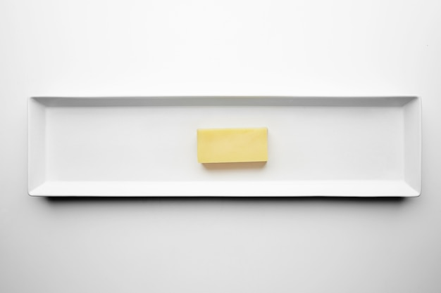 Brick of mozzarella cheese isolated on white plate, top view. any other solid cheese without holes.