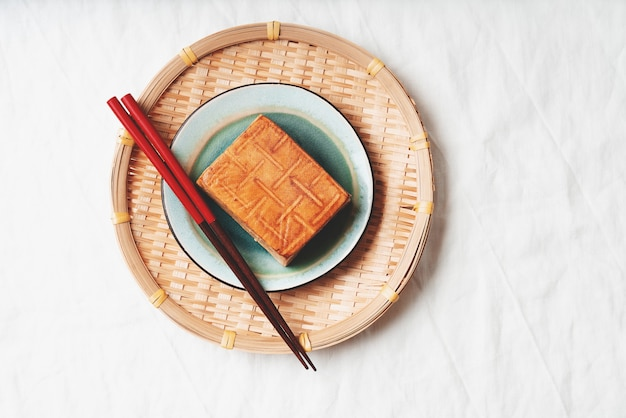 有機燻製豆腐チーズのレンガを竹マットの上に青いプレートで添えました。フラットレイ。上面図。ビーガンスナックのコンセプト
